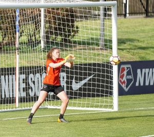 Goal keeper with ball coming towards her